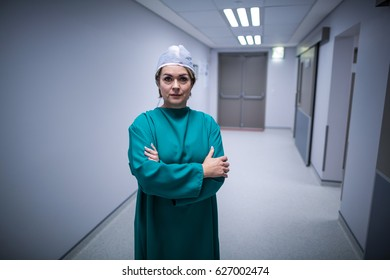 Portrait of female surgeon standing with arms crossed in hospital corridor