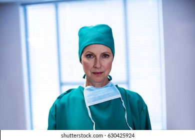 Portrait of female surgeon standing with arms crossed in operation theater of hospital
