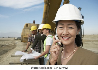 Portrait of a female surveyor in hard hat in front of heavy machinery using cellphone on site
