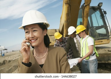 Portrait of a female surveyor in hard hat in front of workers and heavy machinery using cellphone on site