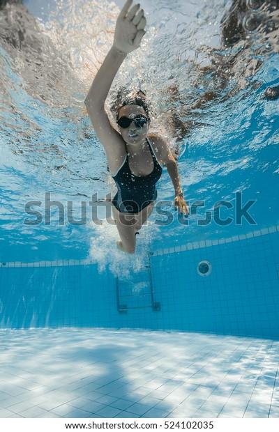 プールに飛び込んで飛び込む女性の泳ぎ手のポートレート。スポーティー ...