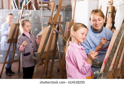 Portrait female teacher helping girl during painting class at art classes
