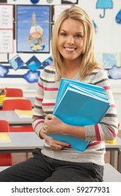 Portrait Of Female Teacher Sitting At Desk In Classroom