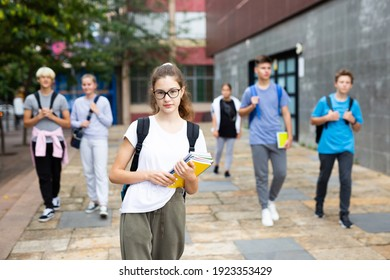 Portrait of female teenage student with workbooks in hands on her way to college on autumn day. Back to school concept.