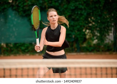 Portrait of a female tennis player in action. Agile woman keeping her racket ready to hit a ball.