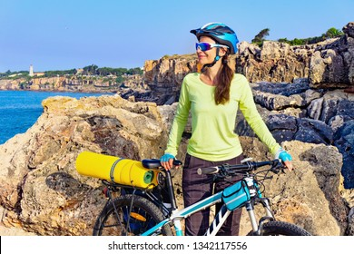 Portrait of female tourist cyclist on the rocky shore on the lighthouse background. Portugal, Europe.