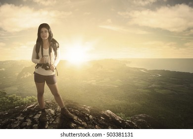 Portrait of female tourist standing on the rock while carrying backpacks and camera with valley view in the background