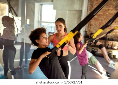 Portrait of female trainer helping teenage boy while he is training using fitness straps in gym. Sport, healthy lifestyle, physical education concept. Horizontal shot. Selective focus