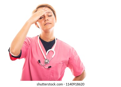 Portrait of female vet wearing pink scrub showing headache gesture isolated on white background with copyspace advertising area