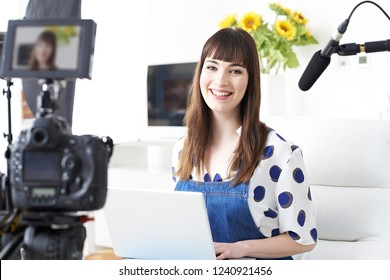 Portrait Of Female Vlogger Recording Broadcast At Home