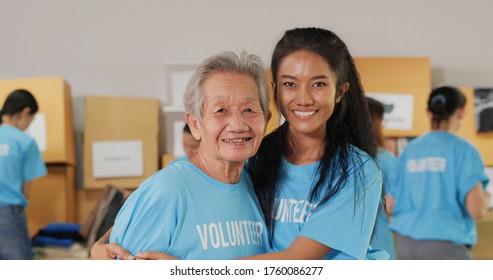 Portrait von weiblichen Freiwilligen und ihrer Mutter posiert mit attraktivem Lächeln zur Kamera. Freiwillige, soziale Unterstützung und Spenden Konzept.