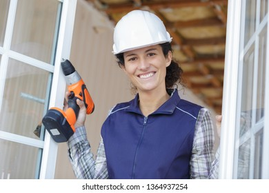 portrait of female window fitter holding cordless drill