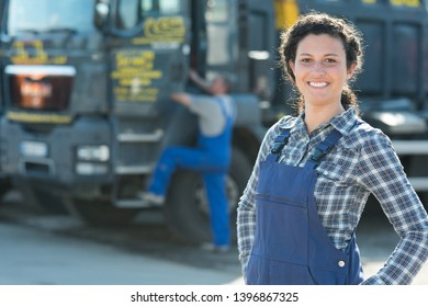 portrait of female worker with articulated lorry in background