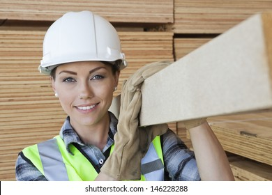 Portrait of female worker carrying wooden plank on shoulder