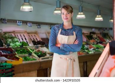 portrait of female worker in green grocers