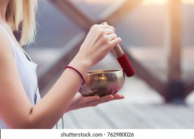 Portrait of Female yoga teacher playing tibetan bowl or singing bell on a wooden bridge on nature at yoga retreat, close up on hands