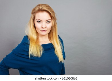 Portrait of feminine blonde young woman wearing dark top shirt having serious, confident face expression.