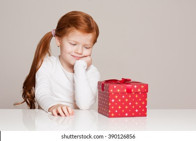 Portrait of a festive little girl with gift box.