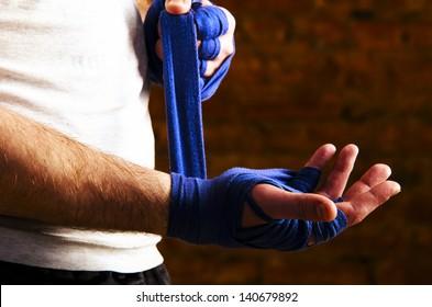 portrait of fighteris applying bondage tape on hands