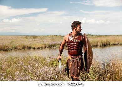 Portrait of fighting ancient warrior in armor with sword and shield.  Spartan Soldier. Landscape background