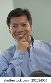 Portrait of a Filipino business executive seated in a conference room with his hand holding his chin.