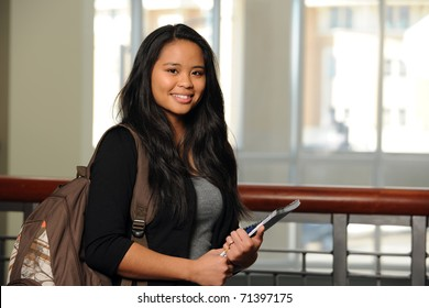Portrait of Filipino girl with notebook and backpack indoors