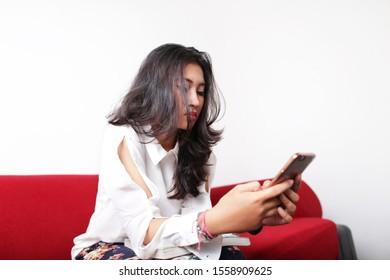 portrait filipino woman using smartphone on white background