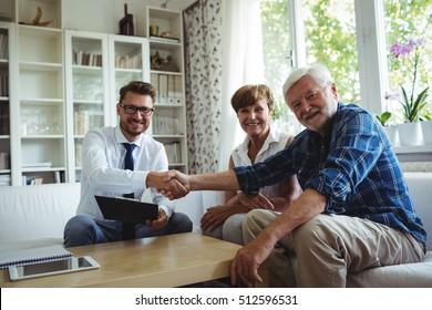 Portrait of financial advisor shaking hands with senior man in living room