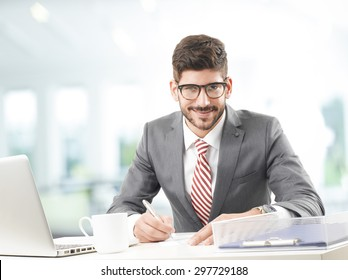 Portrait of financial advisor sitting at office in front of computer and working on business plan. Young businessman holding hands pen and making calculations.
