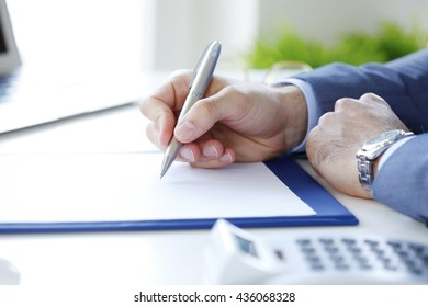 Portrait of financial businessman signing the contract while sitting at desk.
