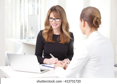 Portrait of financial consultant sitting with her client while discussing at office.