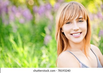 Portrait of fine charming girl which smiles against summer green park.
