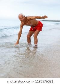 Portrait of fine mature man checks the water temperature on the beach