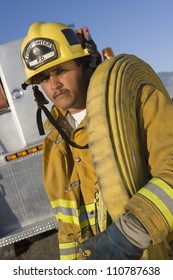 Portrait of a fire fighter carrying fire hose on shoulder