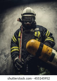 Portrait of firefighter in safety uniform holding yellow oxygen tank.