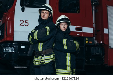 portrait of firefighters in fireproof uniform and helmets with arms crossed standing near truck at fire station