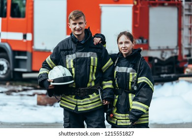 portrait of firefighters in fireproof uniform standing on street with fire truck behind
