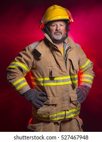 Portrait of Fireman Fire Fighter with red smoke background.  He is wearing a helmet and fire turnouts.