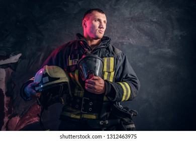 Portrait of a fireman in uniform holding a helmet and oxygen mask standing in the studio against a dark textured wall