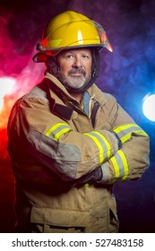 Portrait of a fireman wearing Fire Fighter turnouts and helmet.  Background is red and blue smoke and light.  Turnouts are protective clothing.