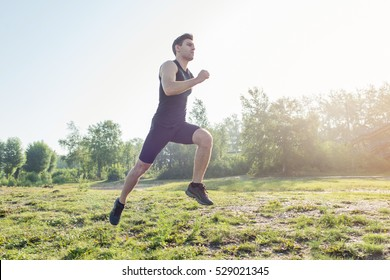 Portrait of fit athletic man jogging on the street in morning summer day. Outdoors training in fresh air