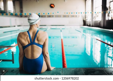 Portrait of a fit female swimmer by the pool at leisure center