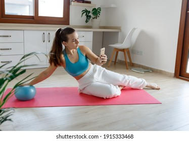 Portrait of fit and healthy gym woman with small pilates ball making exercise on yoga mat at home,holding phone.New reality
