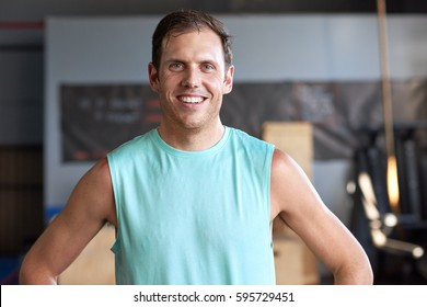 Portrait of fit healthy man happy in sportswear smiling in gym, fitness lifestyle concept