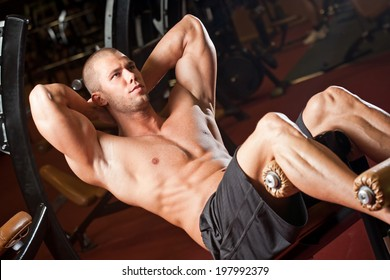 Portrait of a fit lean young man exercising in a gym.