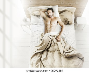Portrait of fit male model asleep in luxurious bedroom bathed in bright warm morning window light