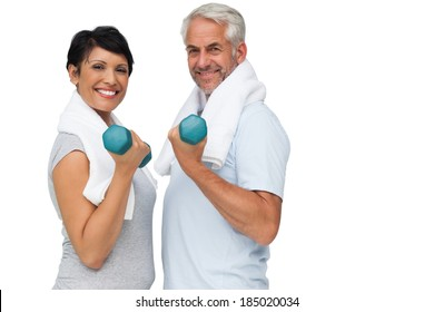 Portrait of a fit mature couple exercising with dumbbells over white background