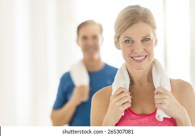 Portrait of fit mature woman holding towel around neck with man in background at home
