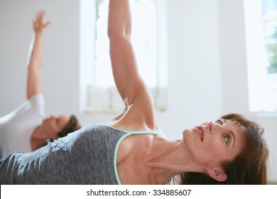 Portrait of a fit mature woman performing a yoga routine at gym. Bending over and looking away with her arms outstretched. Ardha Chandrasana, half Moon pose.