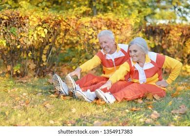 Portrait of fit senior couple exercising in autumn park